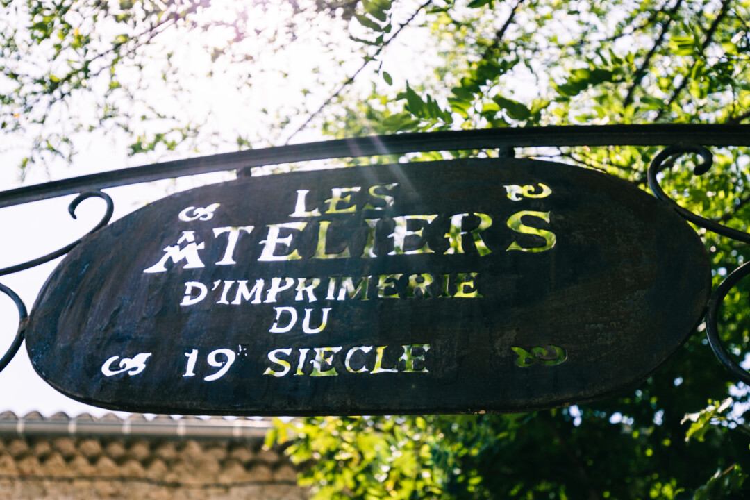 """Panneau en fer avec des lettres évidées indiquant """"Les ateliers d'imprimerie du 19 siecle"""""""