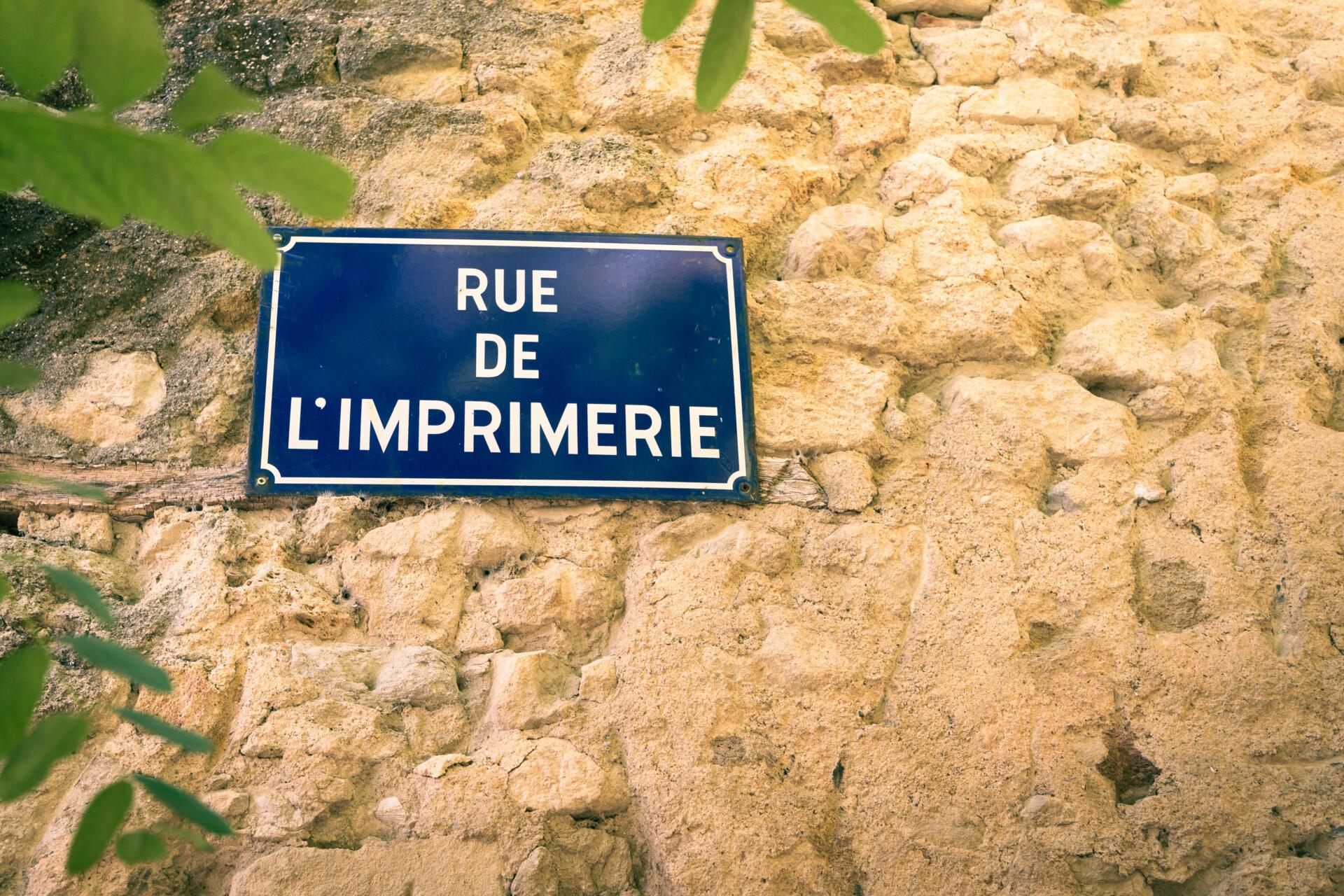 """Panneau de rue sur un mu en pierre indiquant """"Rue de l'imprimerie"""""""