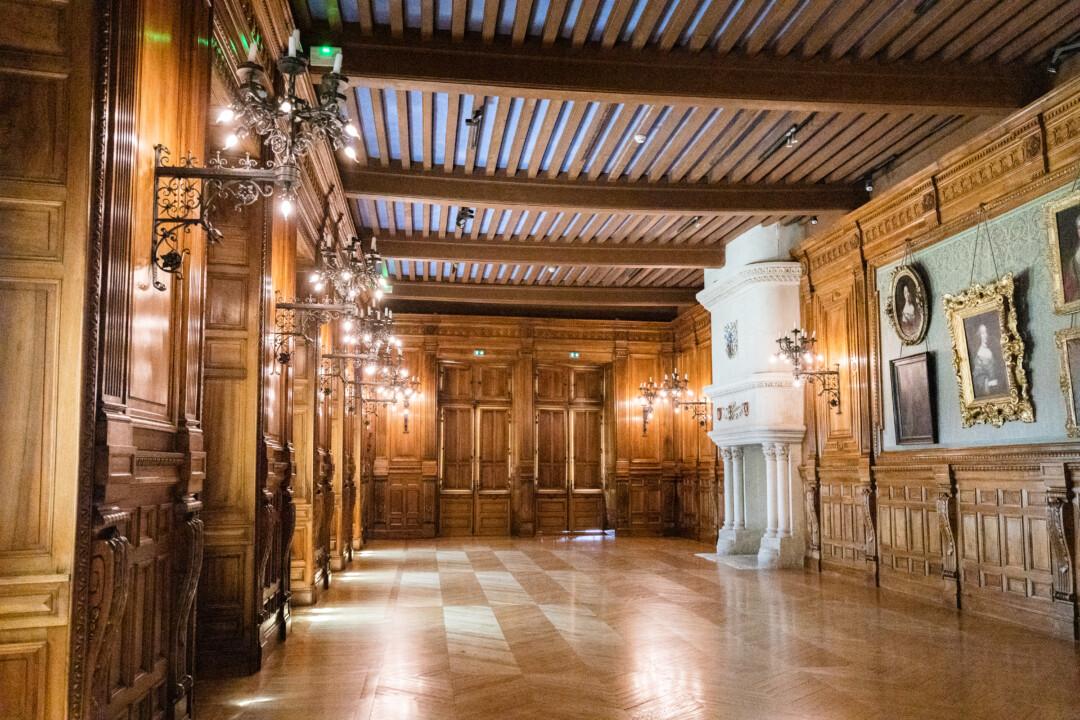 Salle du château de Grignan. Les murs sont couverts de bois et papier peint, avec quelques peintures accrochée. Des chandeliers en fer forgé sont également fixés à ces derniers à intervalles réguliers. On aperçoit dans le fond une massive cheminée en pierre claire.